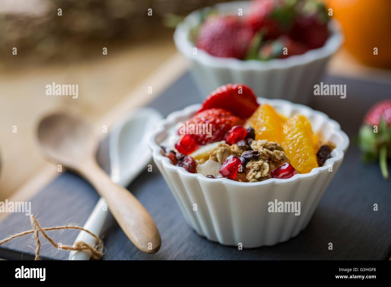 Muesli con arancia, fragola, Cacao naselli e Melograno su yogurt Immagini Stock