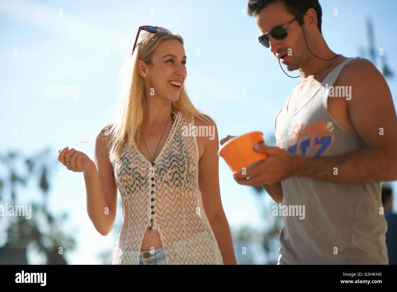 Paio di passeggiare e mangiare yogurt surgelato a Venice Beach, California, Stati Uniti d'America Immagini Stock