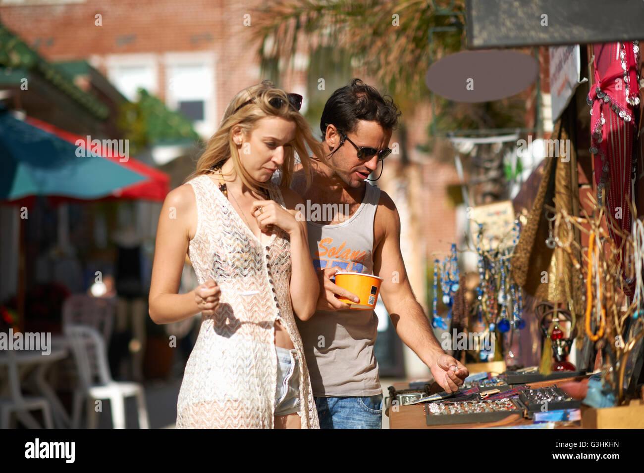 Paio mangiare yogurt surgelato e la navigazione gioielli stallo a Venice Beach, California, Stati Uniti d'America Immagini Stock