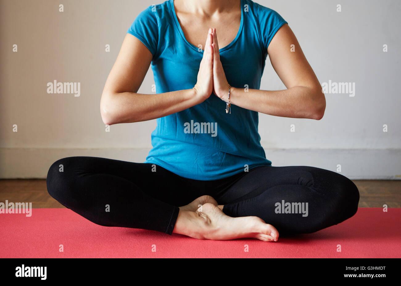 Vista ritagliata della donna seduta croce gambe, mani insieme meditando Immagini Stock