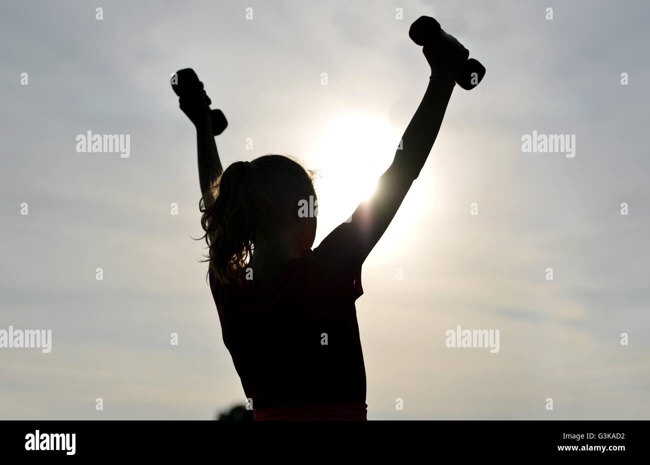Silhouette della ragazza al di fuori esercizio Immagini Stock