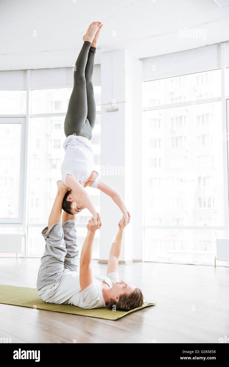 Tranquilla coppia giovane di bilanciamento e facendo acro yoga in studio Immagini Stock
