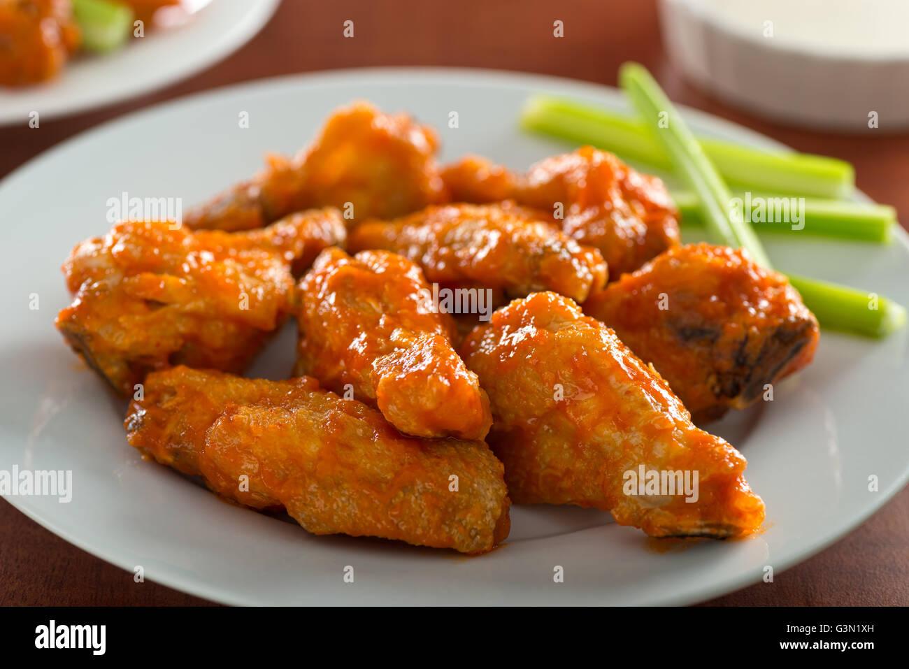 Una piastra di deliziosi piatti piccanti ali di pollo con salsa sriracha e sedano. Immagini Stock