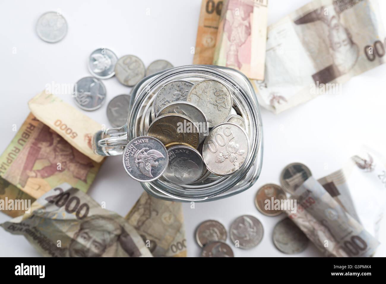 Rupiah moneta all'interno del vasetto con denaro spargere in giro il vaso del frullatore Immagini Stock