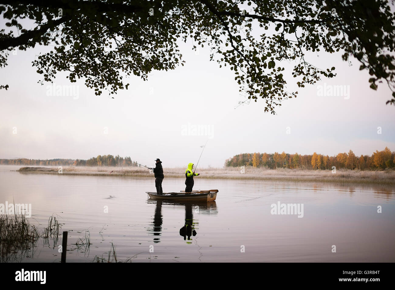 La Svezia, Vastmanland, Bergslagen, Torrvarpen, giovani uomini la pesca nel lago al tramonto Immagini Stock