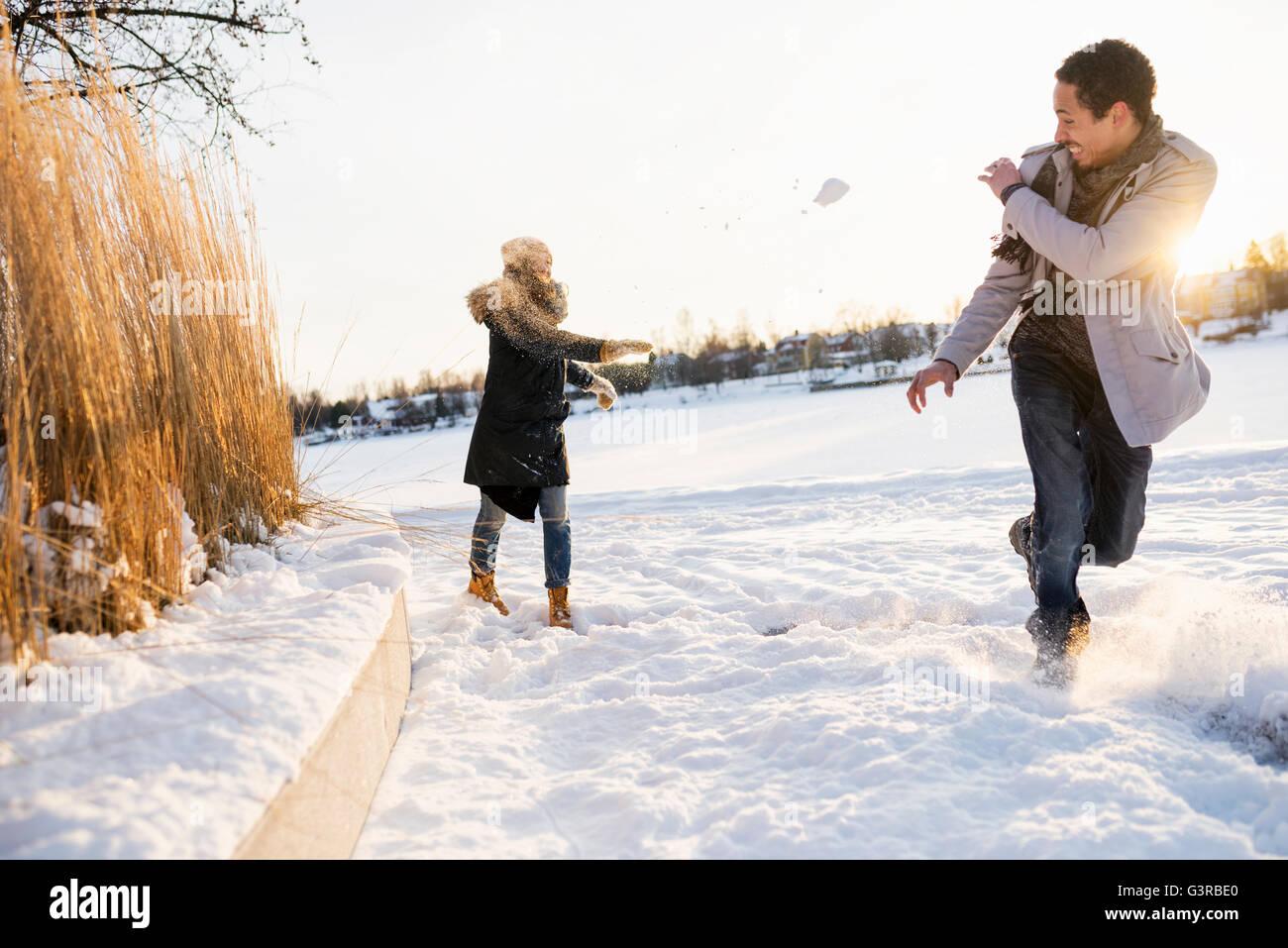 La Svezia Vasterbotten, Umea, coppia giovane godendo lotta con le palle di neve Immagini Stock