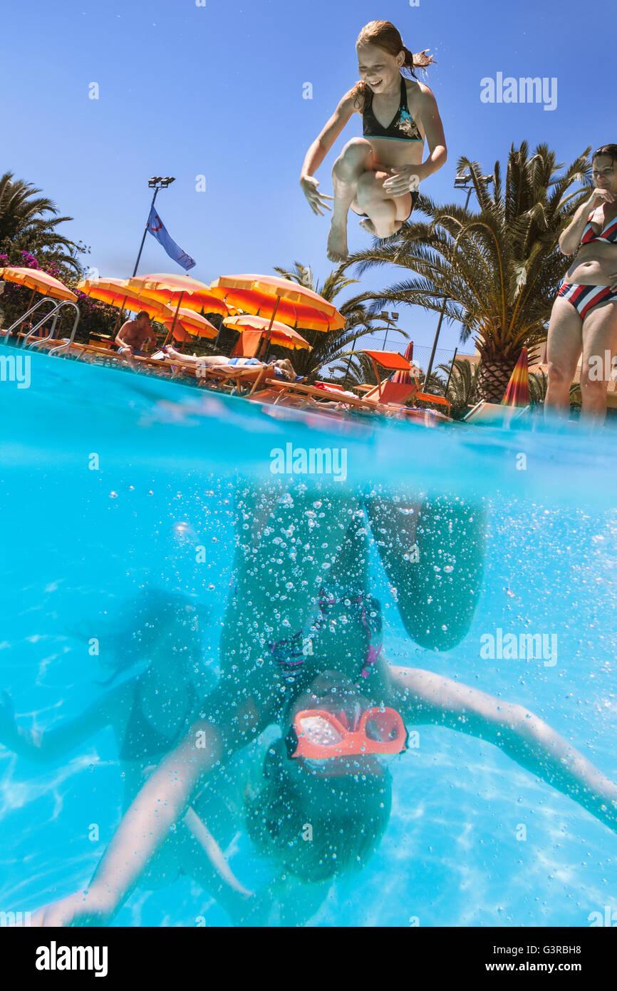 L'Italia, Sardegna, Alghero, Madre guardando i bambini (14-15, 16-17) immersioni in piscina Immagini Stock