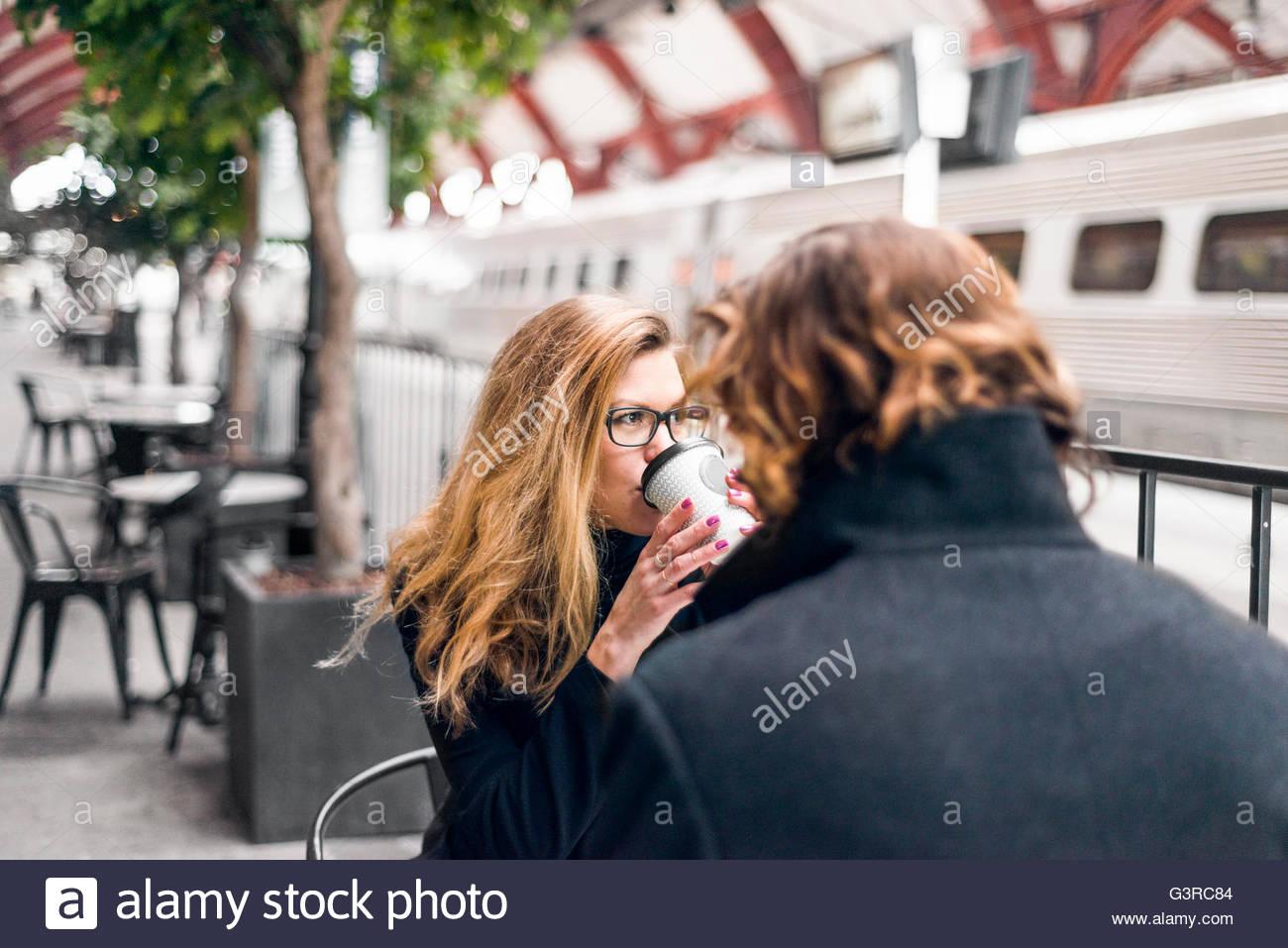 La Svezia, Skane, Malmo, metà donna adulta di bere il caffè al cafè sul marciapiede Immagini Stock