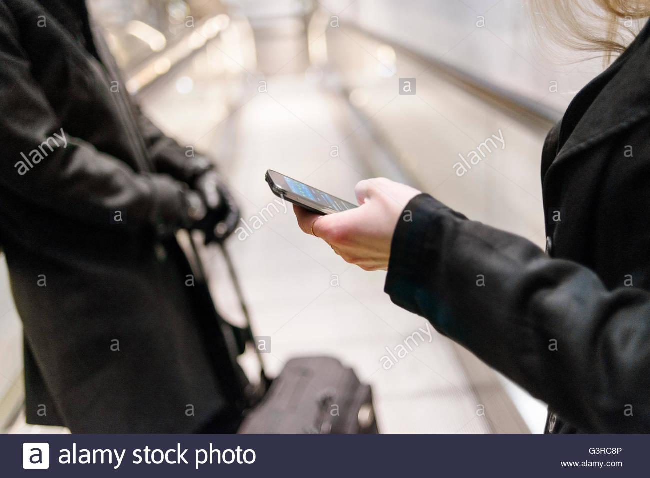 La Svezia, Skane, Malmo, metà sezione di donna texting su escalator Immagini Stock