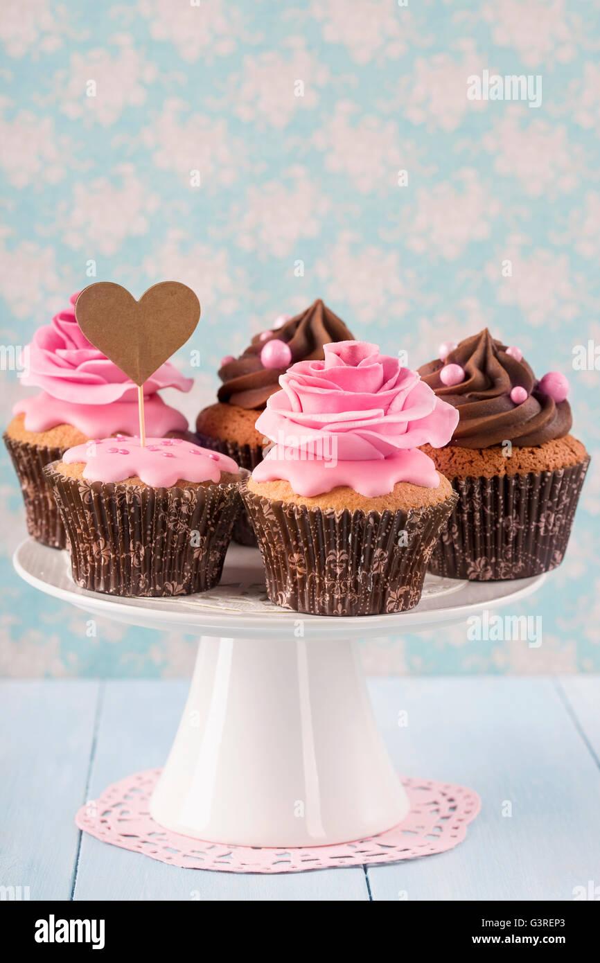 Tortine con dolci rose fiori e un cakepick per testo Immagini Stock