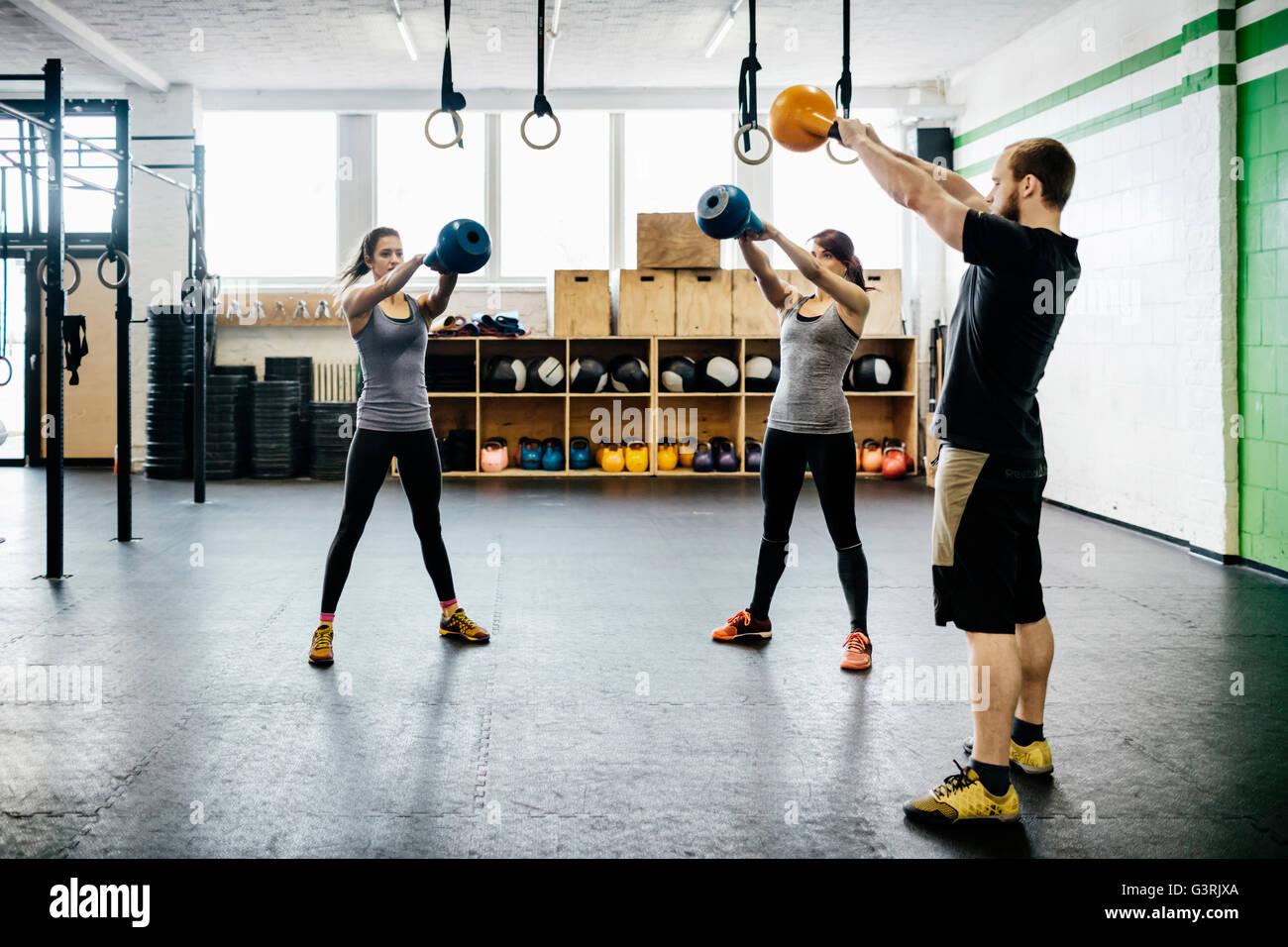 Germania, giovani donne e uomini kettlebells oscillanti in palestra Foto Stock