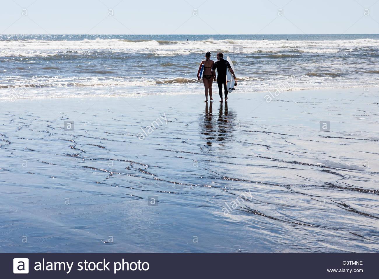 Nuova Zelanda, Auckland, Muriwai Strand, vista posteriore del giovane a piedi con tavole da surf verso il mare Immagini Stock