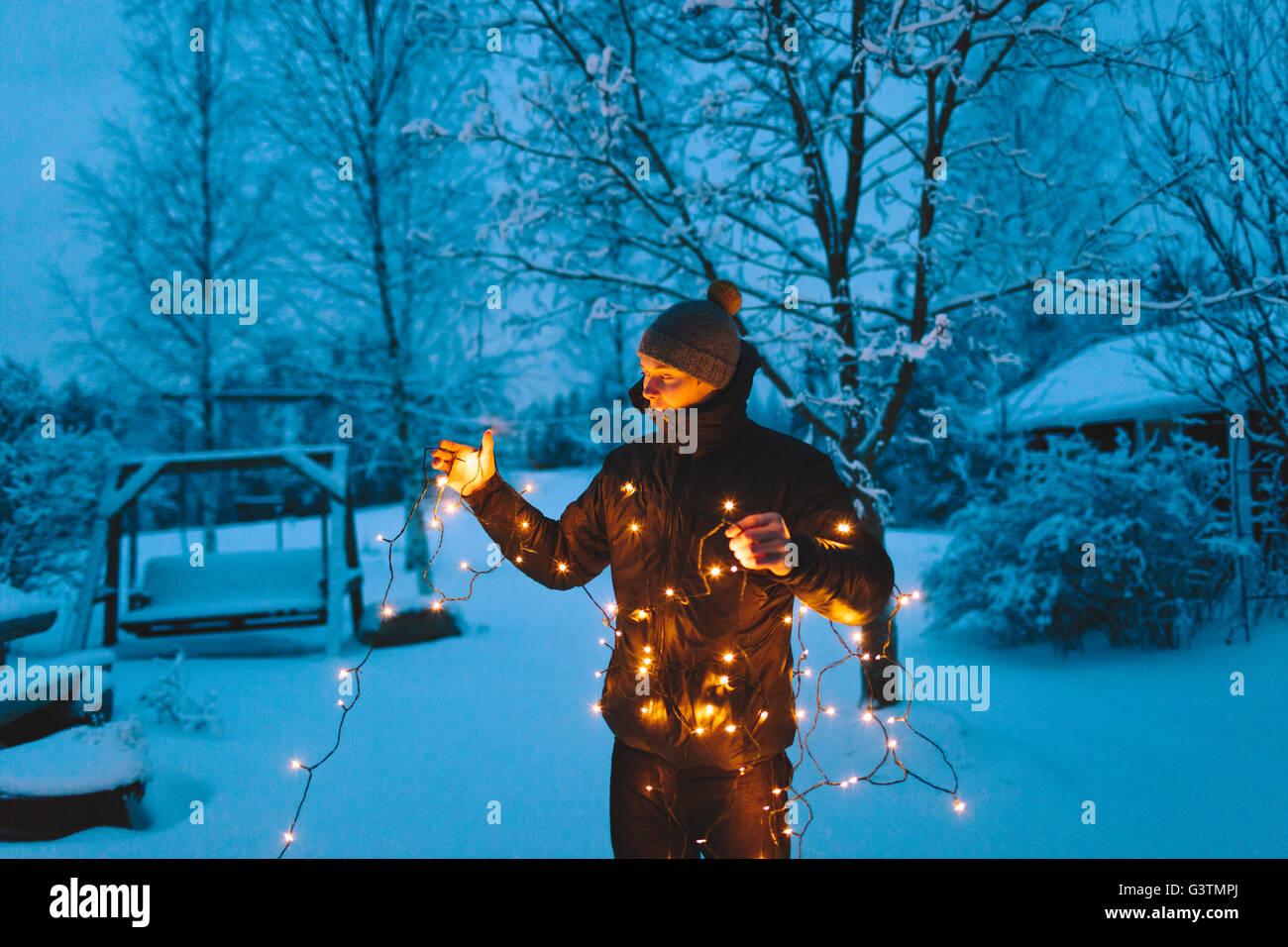 Finlandia, Jyvaskyla, Saakoski, giovane azienda le luci di Natale nel cortile al crepuscolo Immagini Stock
