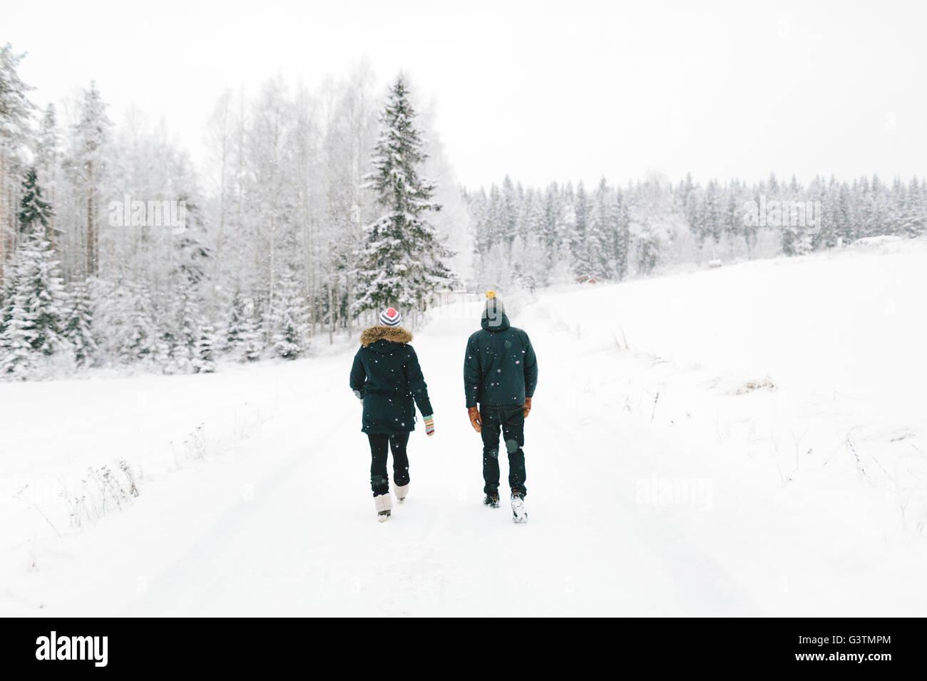 Finlandia, Jyvaskyla, Saakoski, coppia giovane camminando lungo la strada coperta di neve Immagini Stock
