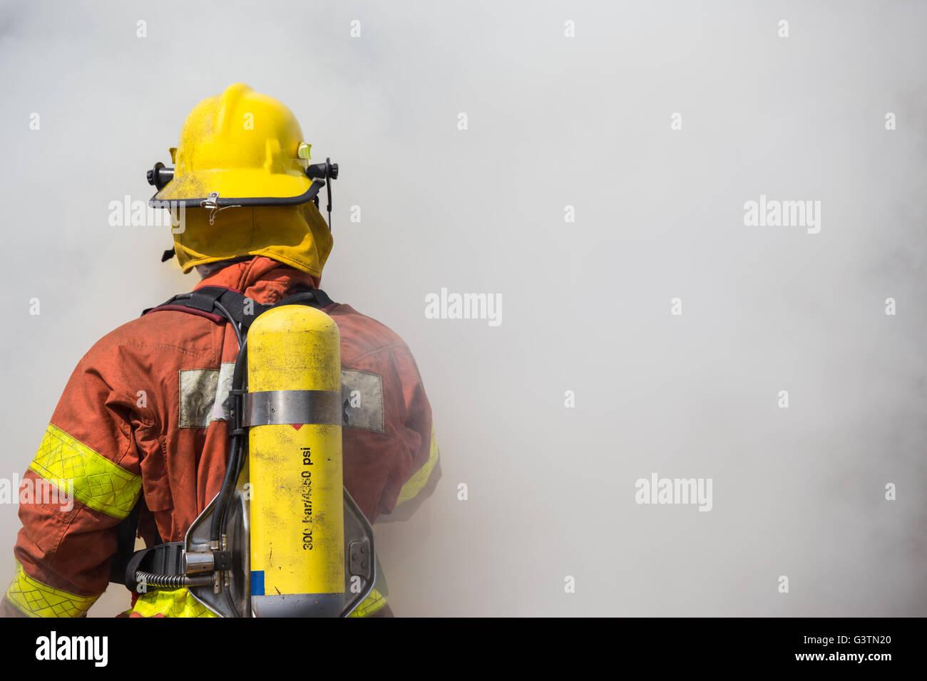 Unico vigile del fuoco sta lavorando e in surround con fumo Immagini Stock