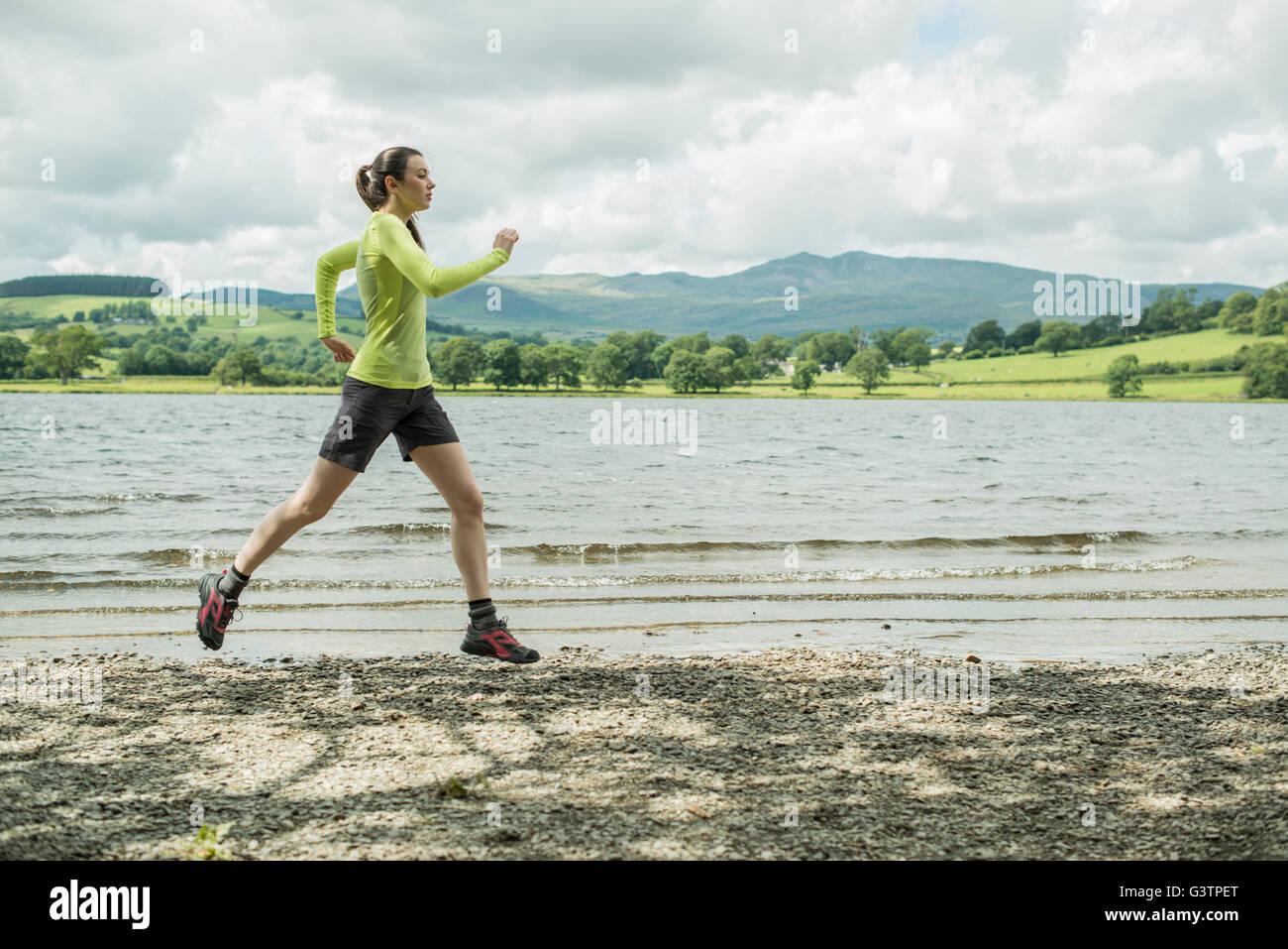 Una ragazza che corre sulla riva accanto a Bala Lake in Galles. Immagini Stock