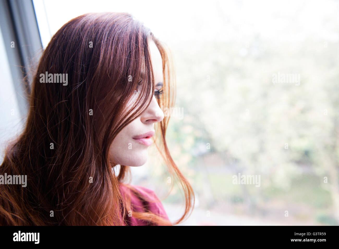 Ritratto di un giovane attraente donna seduta da una finestra. Immagini Stock