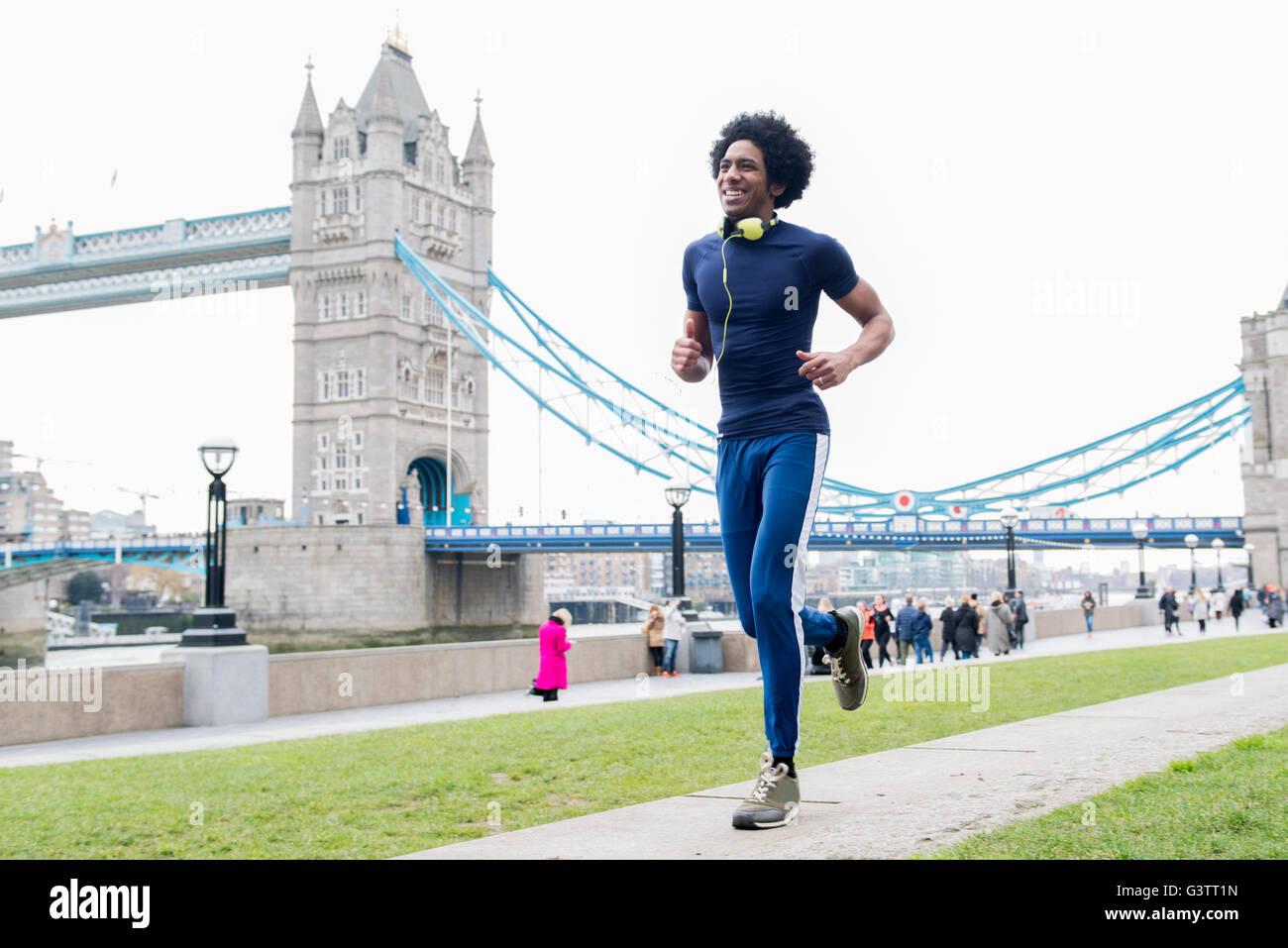 Un giovane uomo jogging passato il Tower Bridge di Londra. Immagini Stock