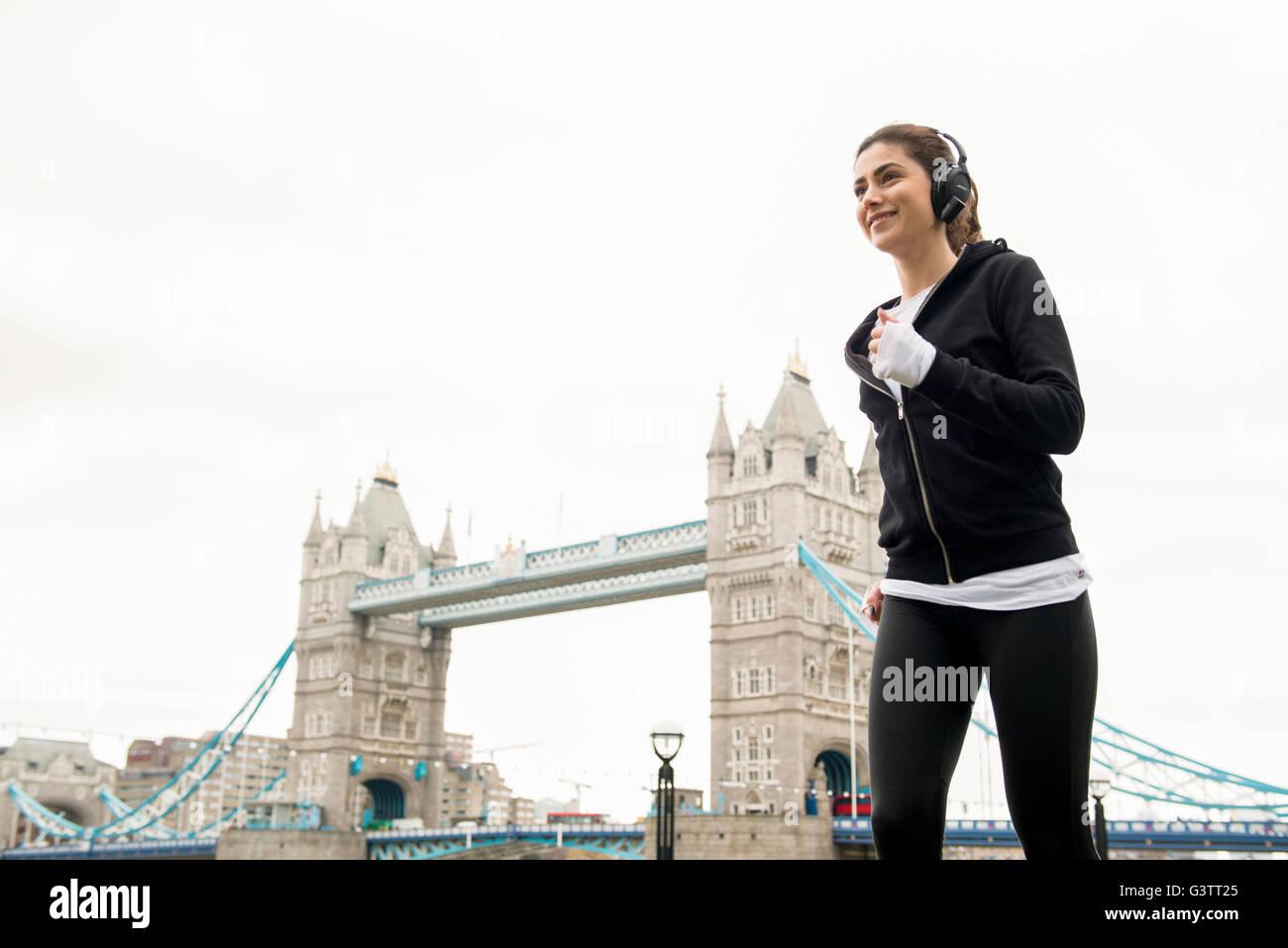 Una giovane donna jogging passato il Tower Bridge di Londra. Immagini Stock