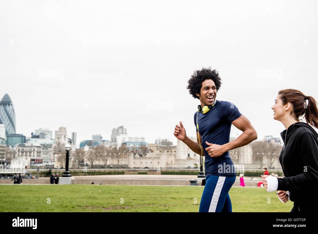 Una giovane coppia jogging insieme passato il Tower Bridge di Londra. Immagini Stock