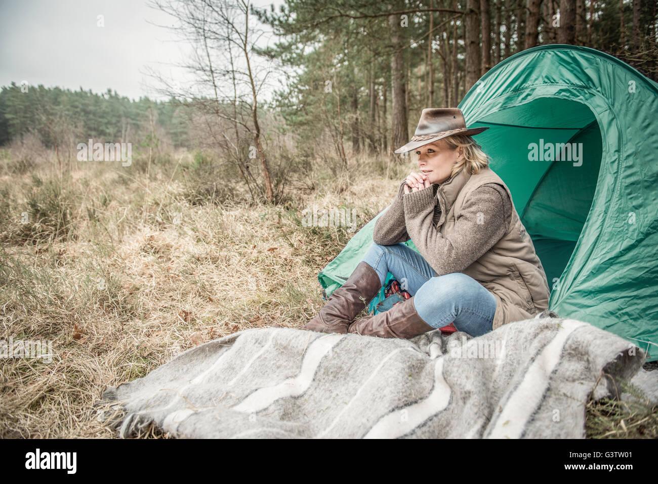 Senior signora seduta godendo il deserto dal suo campeggio. Foto Stock