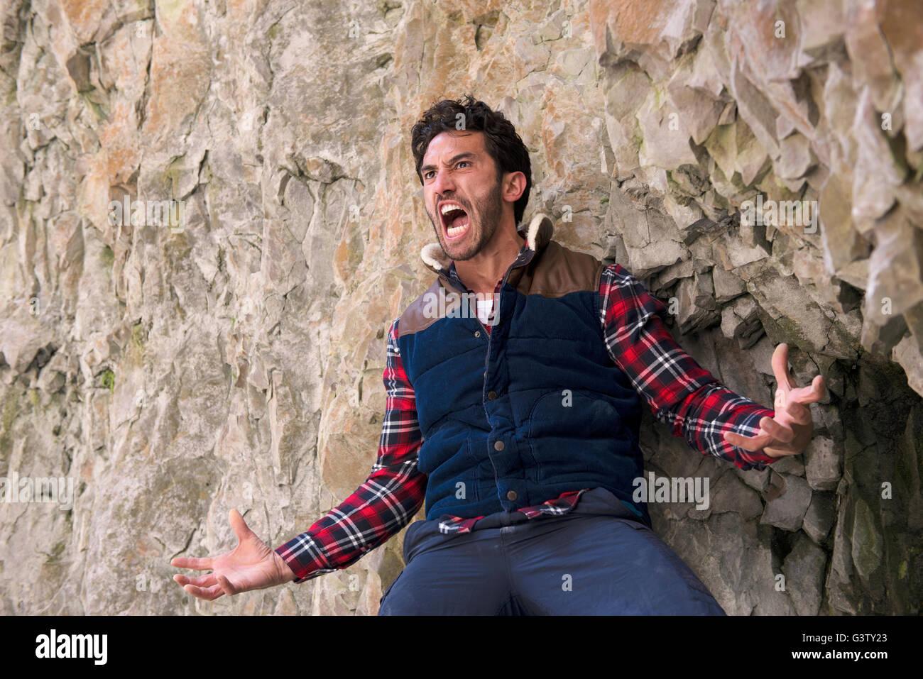 Un scalatore con un espressione di collera in piedi su un listello in terreni accidentati. Immagini Stock