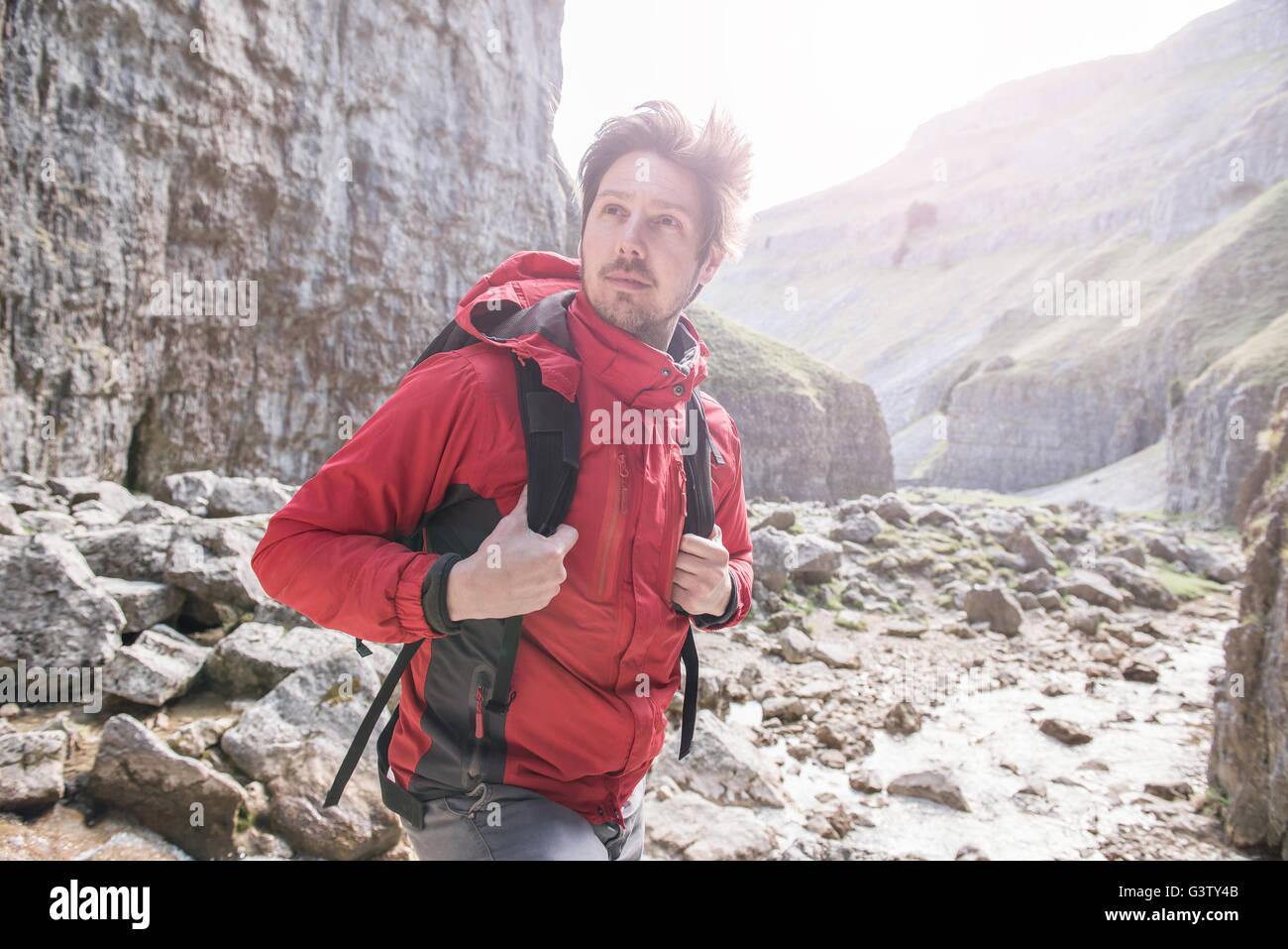 Un scalatore con uno zaino in piedi in un terreno accidentato. Immagini Stock