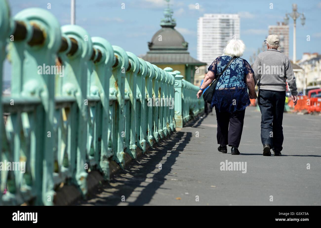 Coppia di anziani tenendo le mani sul lungomare di Brighton, Sussex, Regno Unito Immagini Stock