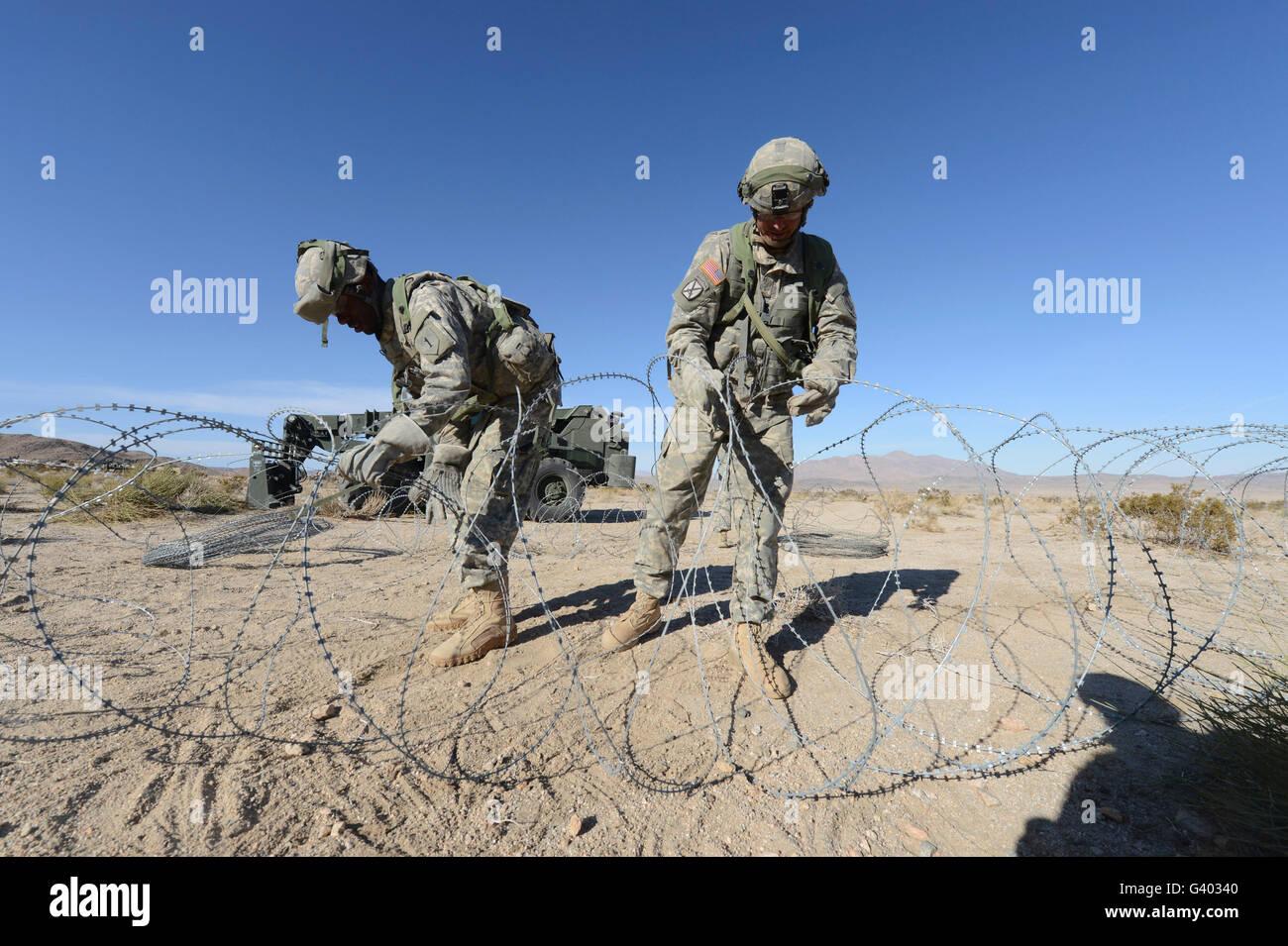 Soldati srotolare il filo di concertina a Fort Irwin, California. Immagini Stock