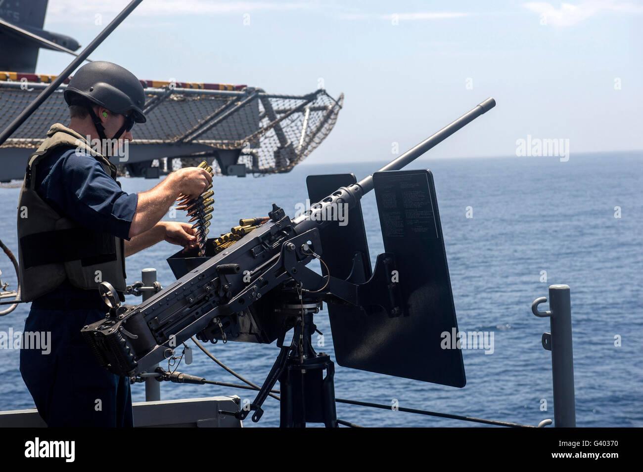 Il tecnico carica un file .calibro 50 mitragliatrice con munizioni. Immagini Stock
