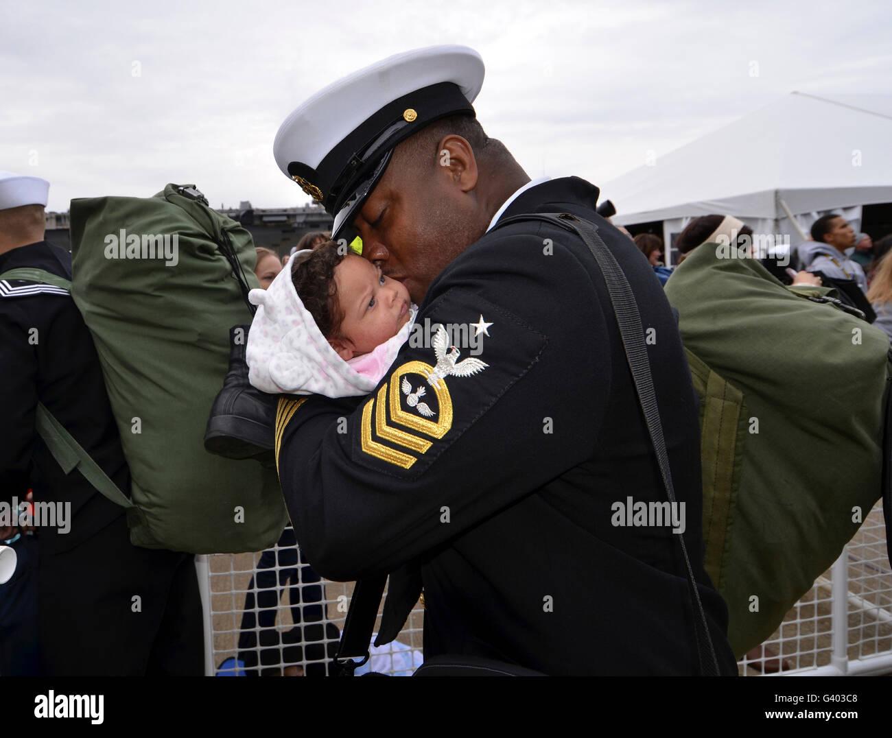Aviation Ordnanceman bacia il suo neonato figlia durante il rientro in patria. Immagini Stock