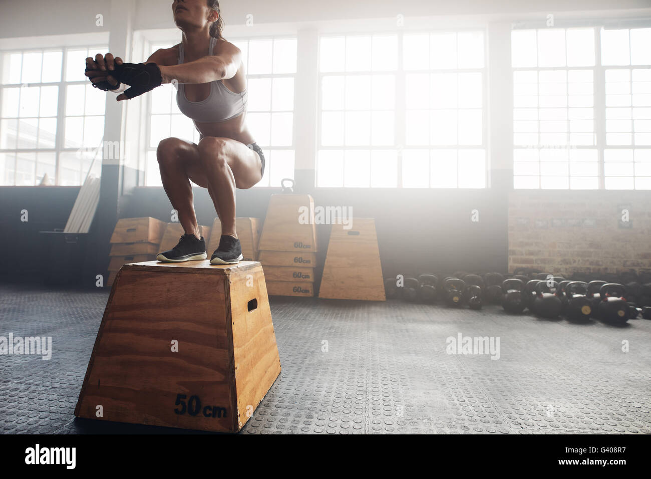 Colpo di una giovane donna di saltare su una scatola come parte di esercizio di routine. Donna Fitness casella facendo Immagini Stock