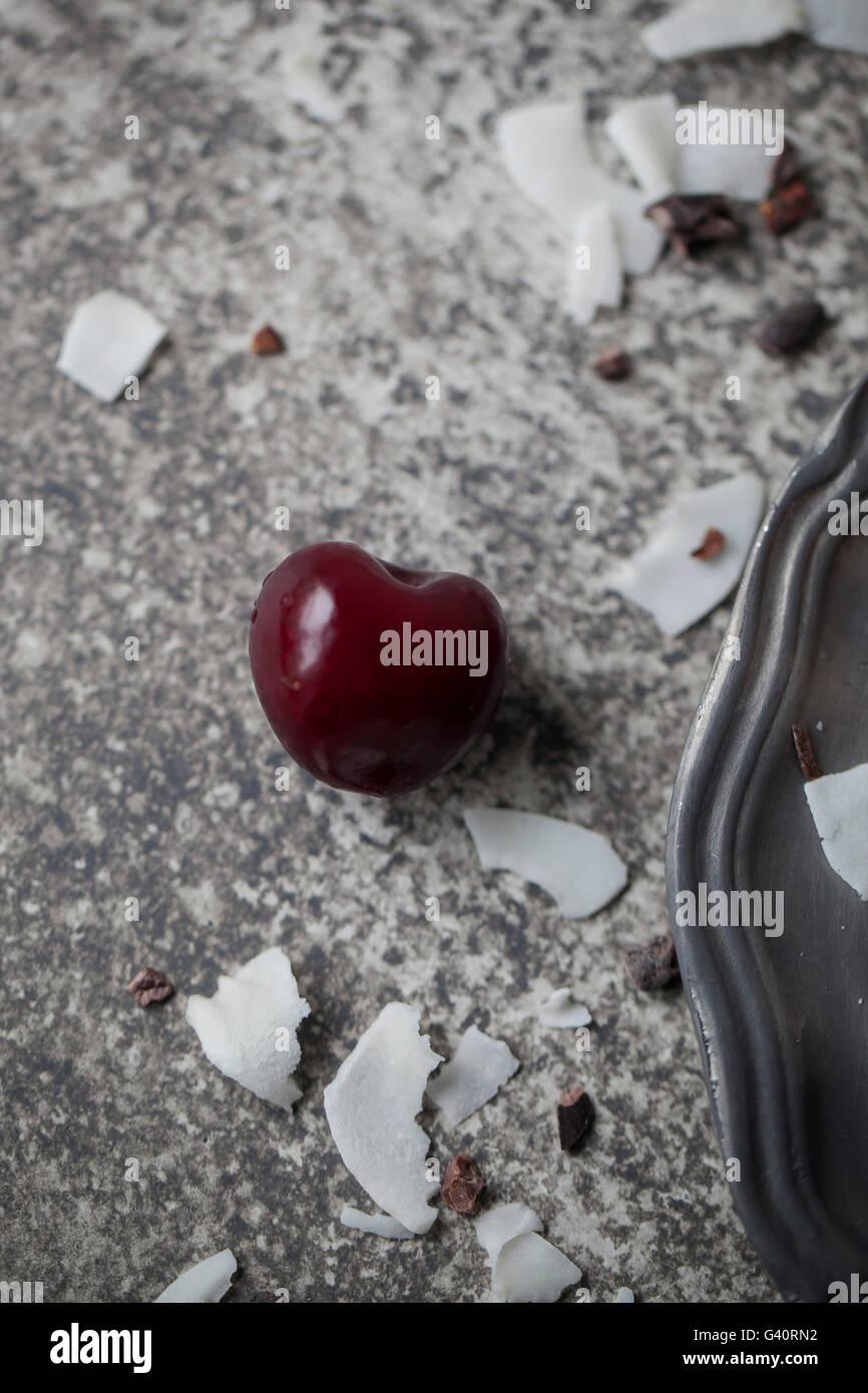 Unico ciliegio e noce di cocco in scaglie su sfondo grigio Immagini Stock
