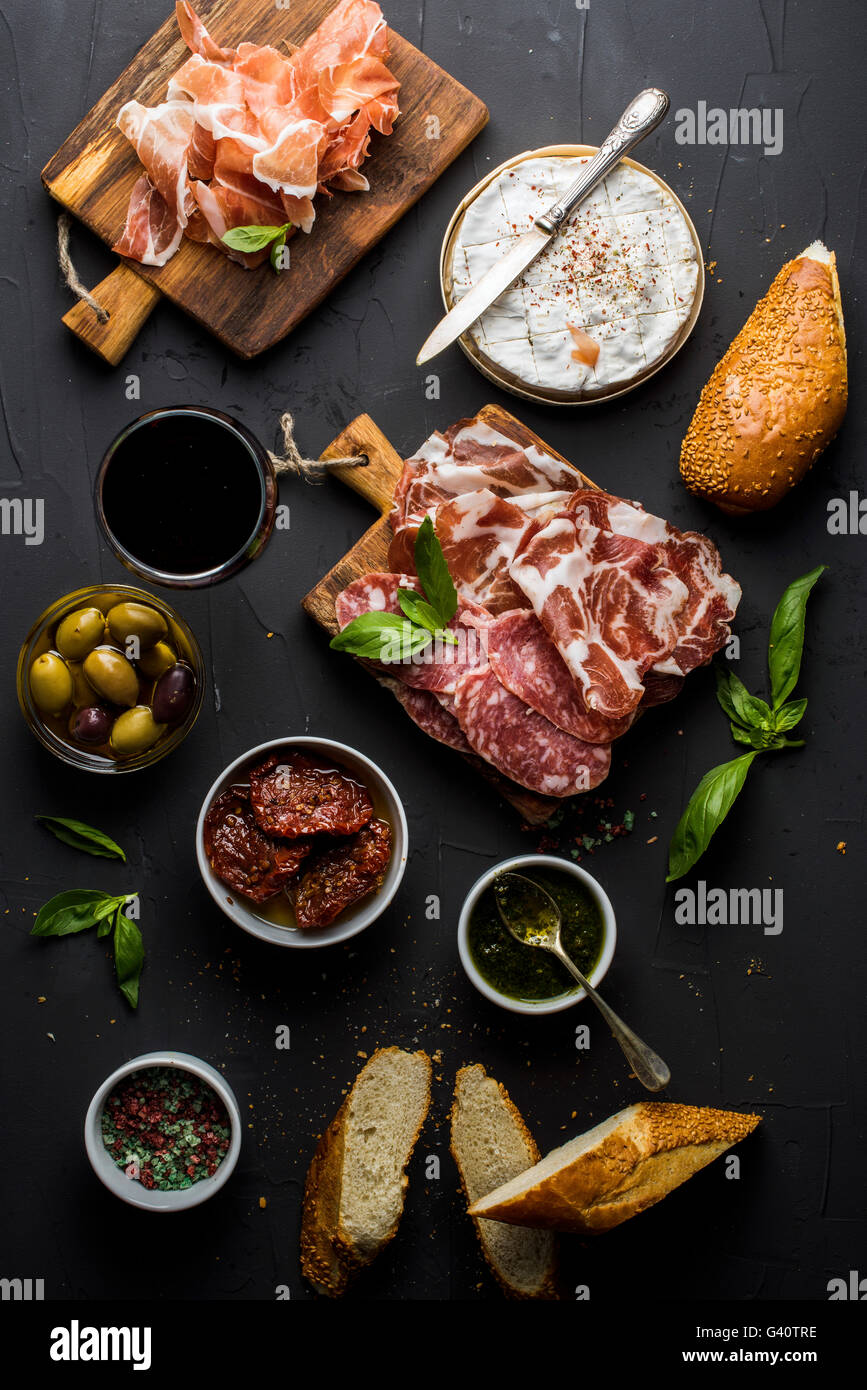 Vino snack set con vuoto tavola di legno in centro. Bicchiere di rosso, selezione di carne, mediterraneo olive, Immagini Stock
