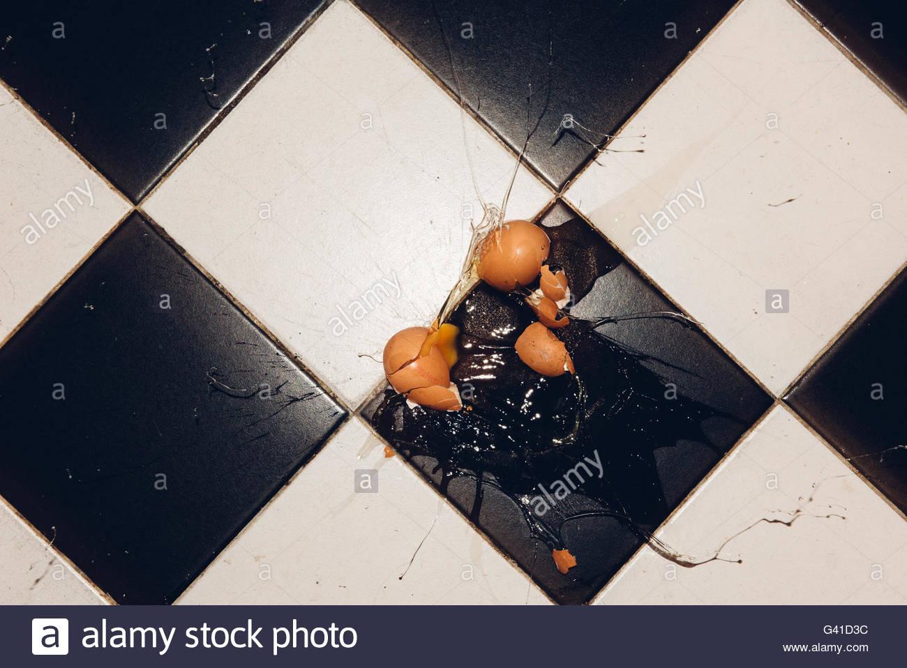 Uova rotte sul pavimento piastrellato con tuorlo d uovo opener e