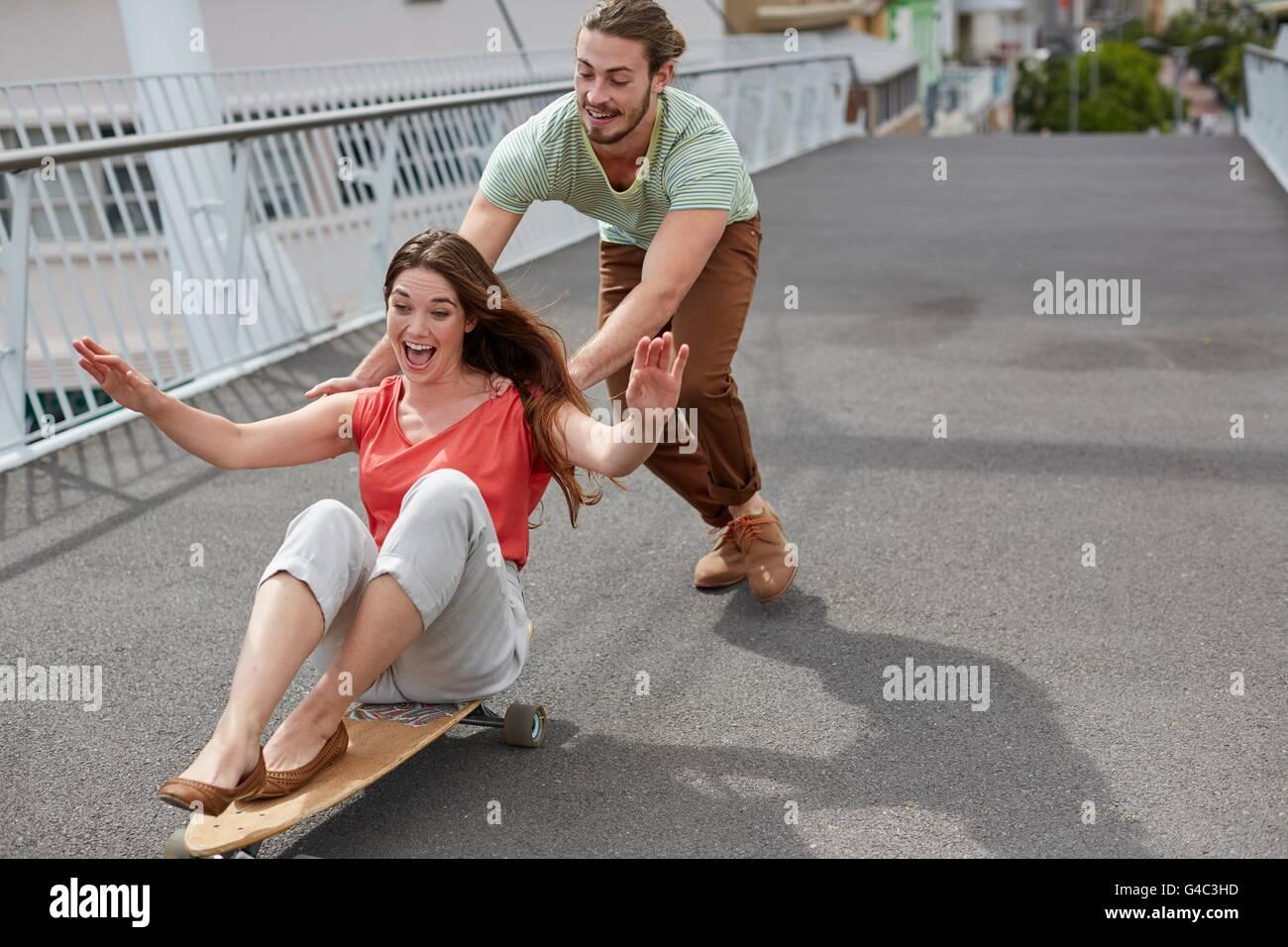 Modello rilasciato. Giovane donna seduta su skateboard con uomo spingendo. Immagini Stock