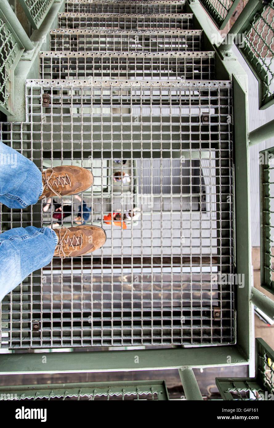 Immagine simbolo circa acrophobia, persona sorge sulla griglia metallica di una scala, guardando in giù nel Immagini Stock