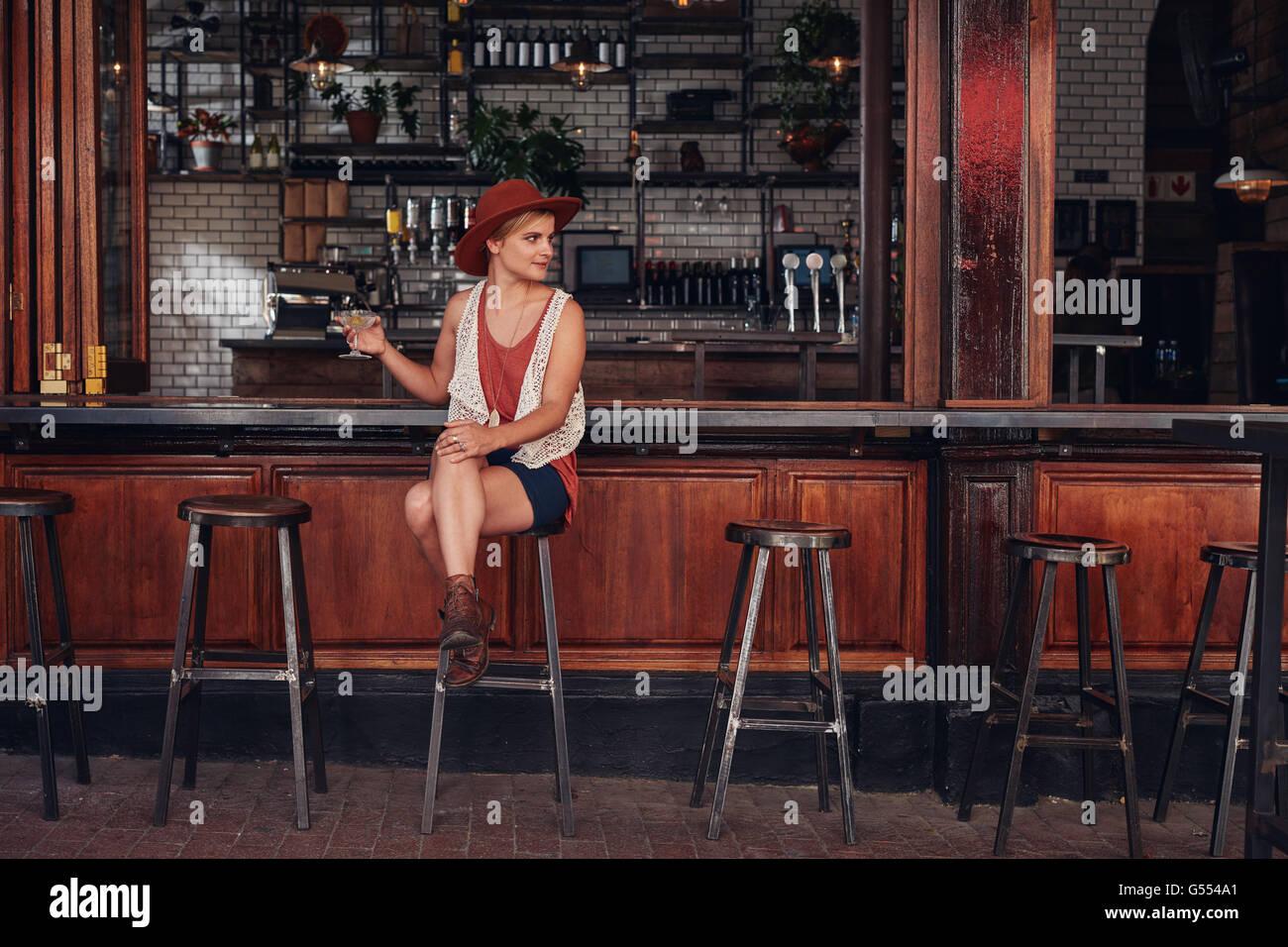 Ritratto di elegante femmina giovane seduto in un bar con bevande e guardando lontano. Bella femmina caucasica presso Foto Stock