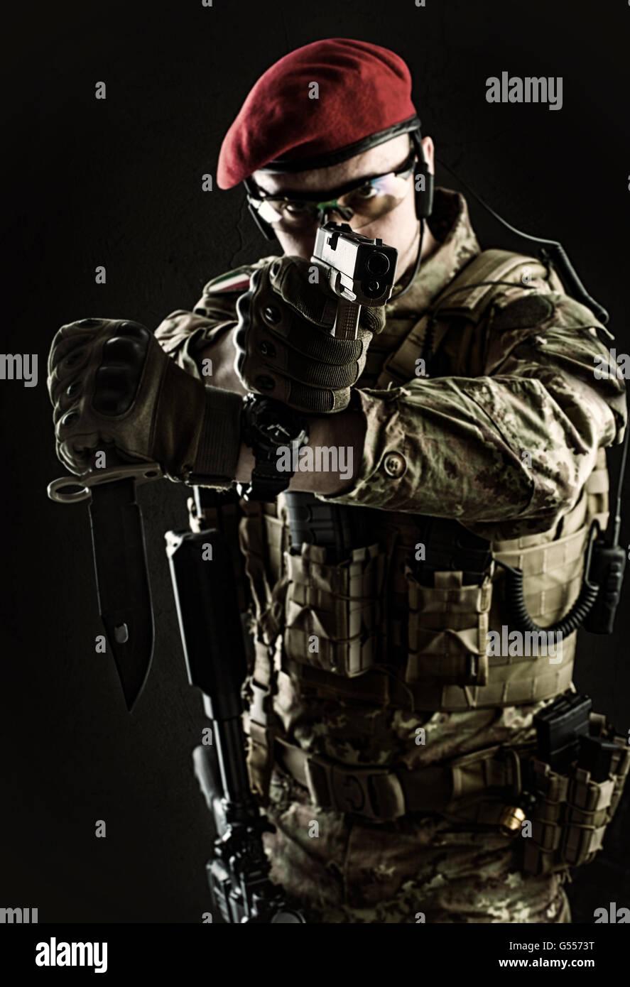 Focus sulla pistola museruola. Bel giovane uomo militare in italiano il camuffamento mirando dalla pistola, egli Immagini Stock