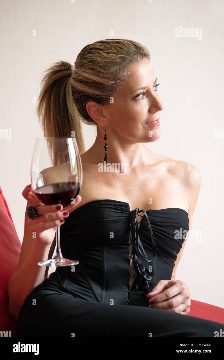 605184bb2467 Donna elegante in un nero abito da cocktail seduti su un divano rosso a  bere un calice di vino rosso