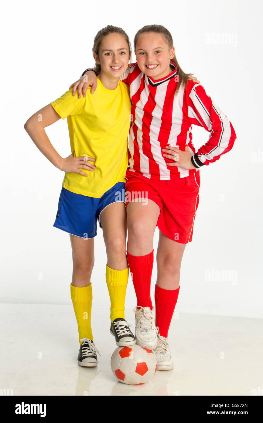 Capitani del team di ragazze partita di calcio in posa con una sfera contro uno sfondo bianco. Entrambi hanno un Immagini Stock