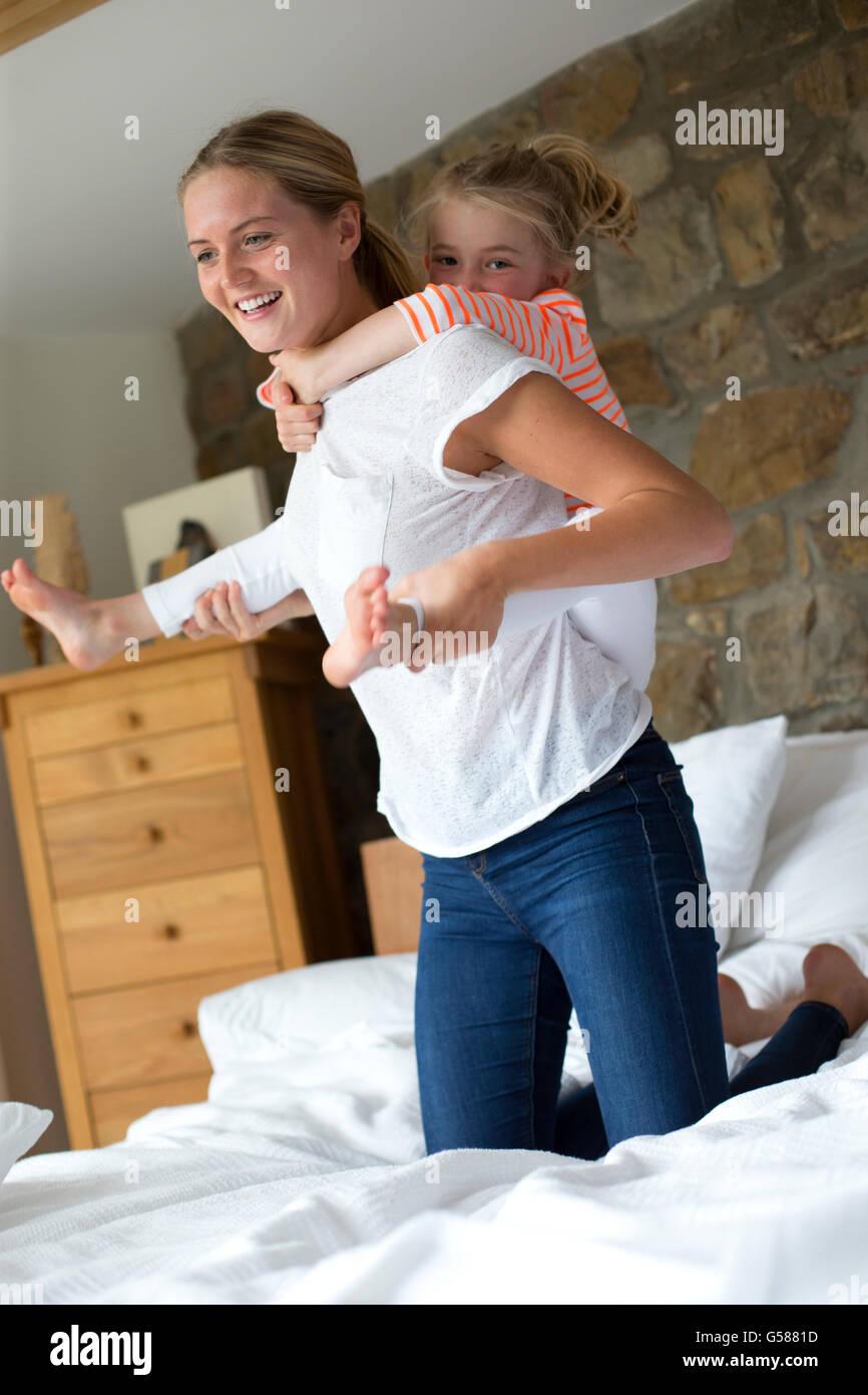 Madre e figlia giocando su un letto di casa Immagini Stock