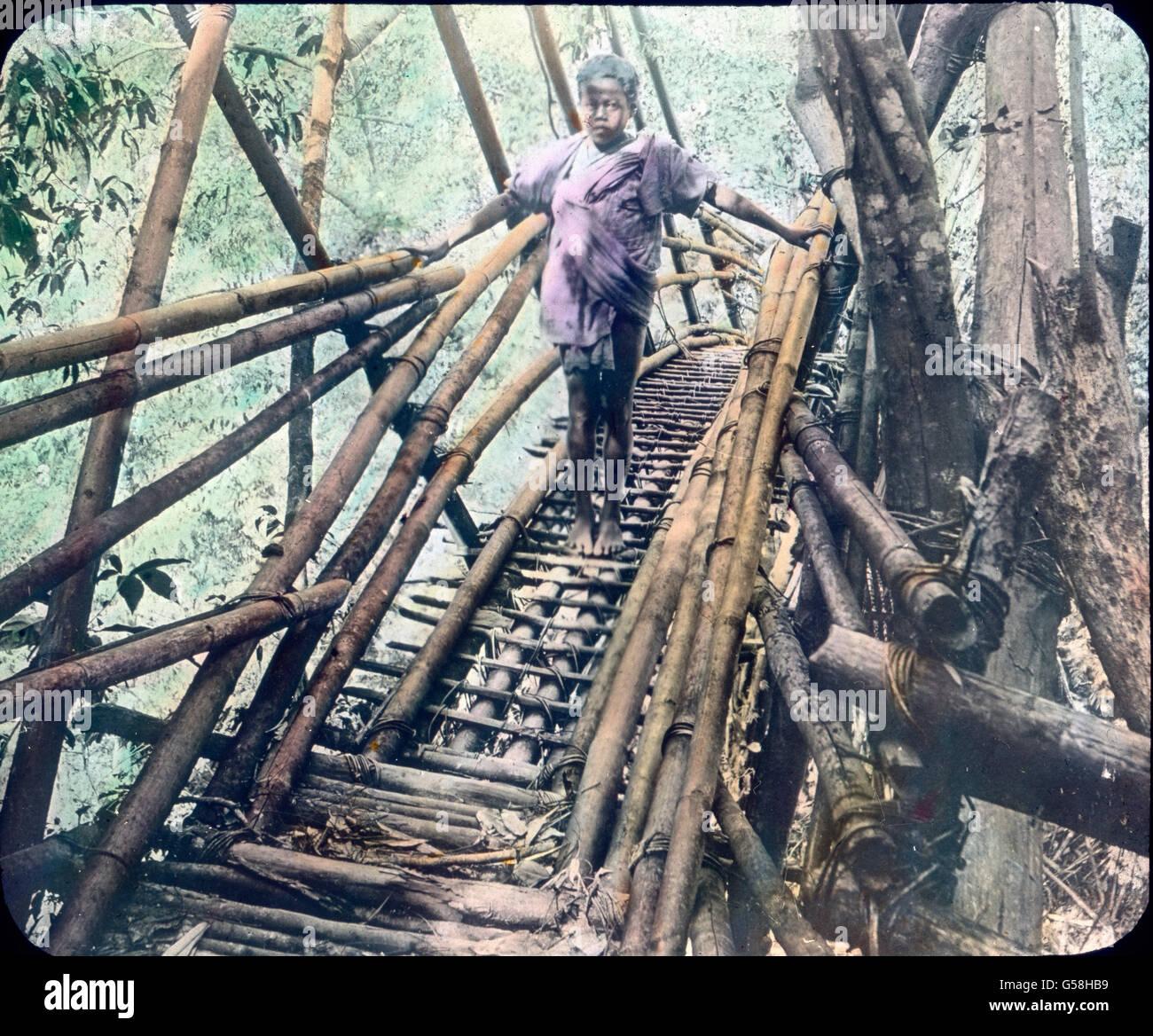 Ein indisches tipo steht auf einer aus Bambus gefertigten Brücke über einer Dschungelschlucht. India, Immagini Stock