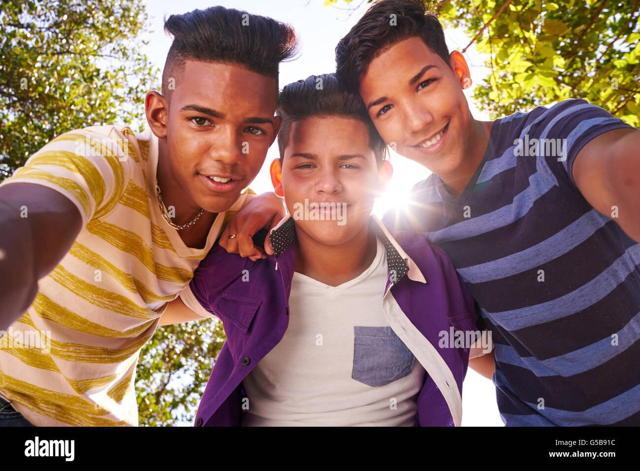 La cultura giovanile, multietnico teens all'aperto abbracciando e cercando felice a telecamera. Immagini Stock