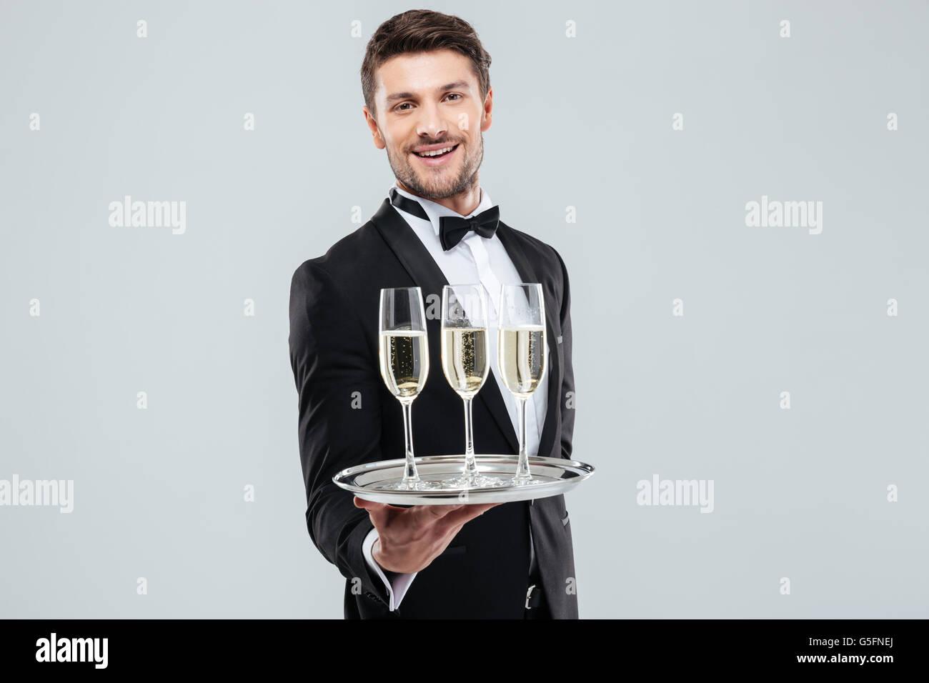 Allegro giovane maggiordomo in smoking sorridente e offrendo champagne Immagini Stock