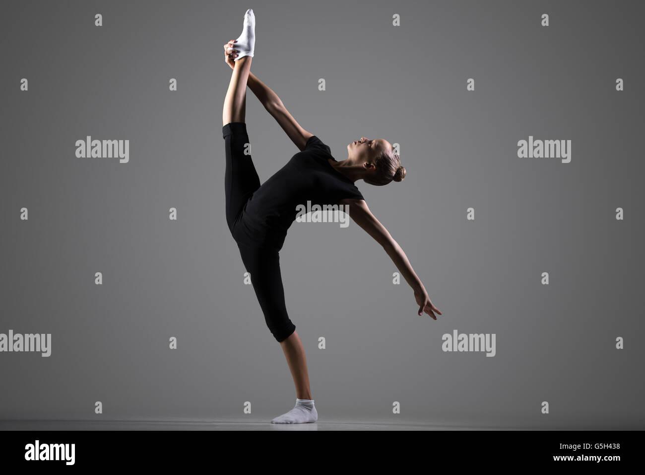 Bella giovane montare ginnasta atleta donna in sportswear, dancing, equilibrio facendo ginnastica ritmica esercizio Immagini Stock