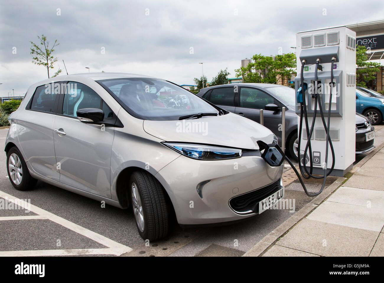 Elettrico di Renault auto in carica in corrispondenza di un punto di ricarica nel parcheggio di un retail outlet Immagini Stock