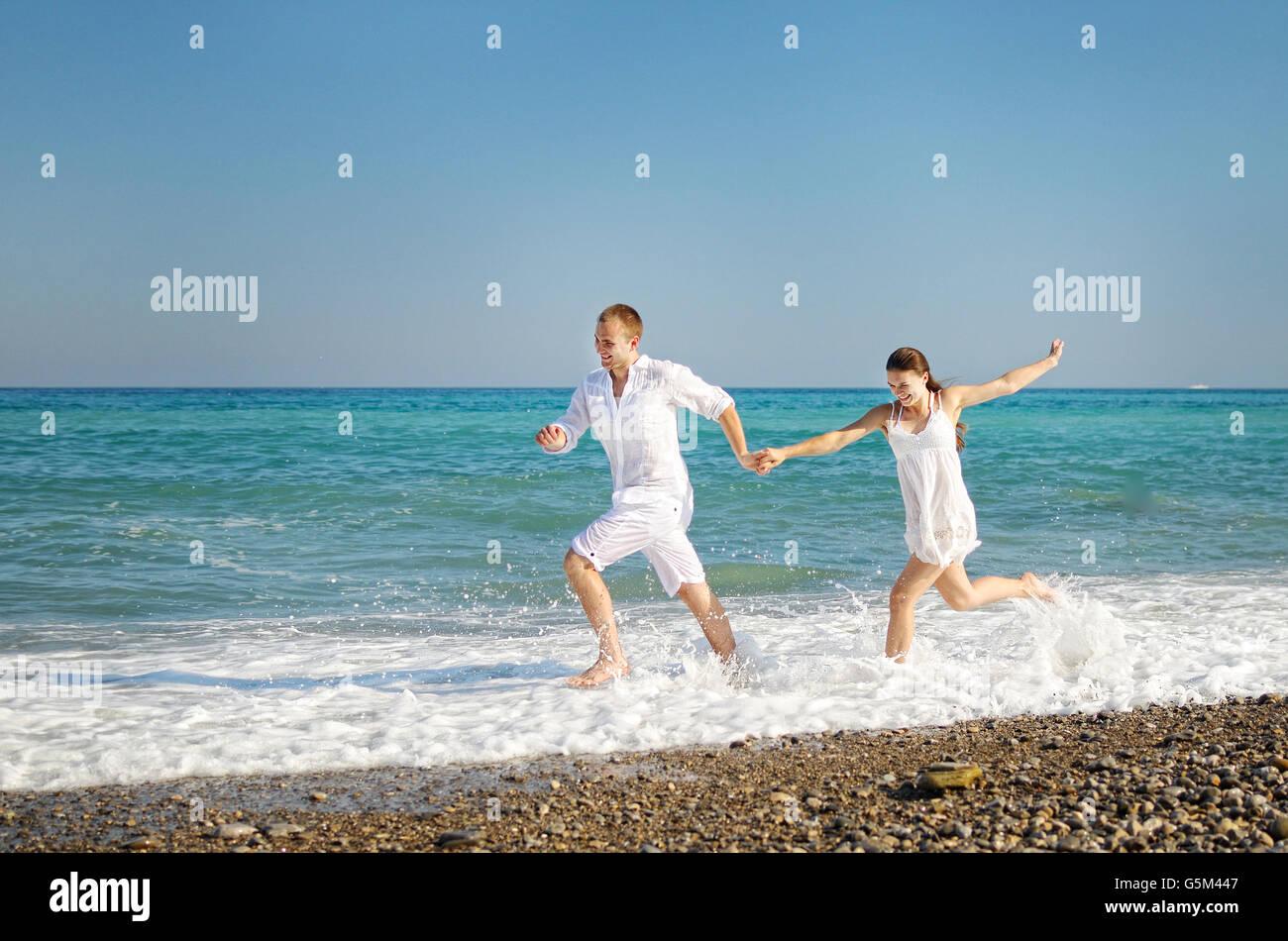 6e1fb410eb35 Felice coppia giovane corre con le mani giunte sulla costa del mare. Il  ragazzo e ragazza vestita di bianco facile vestiti. Sulle facce expressio