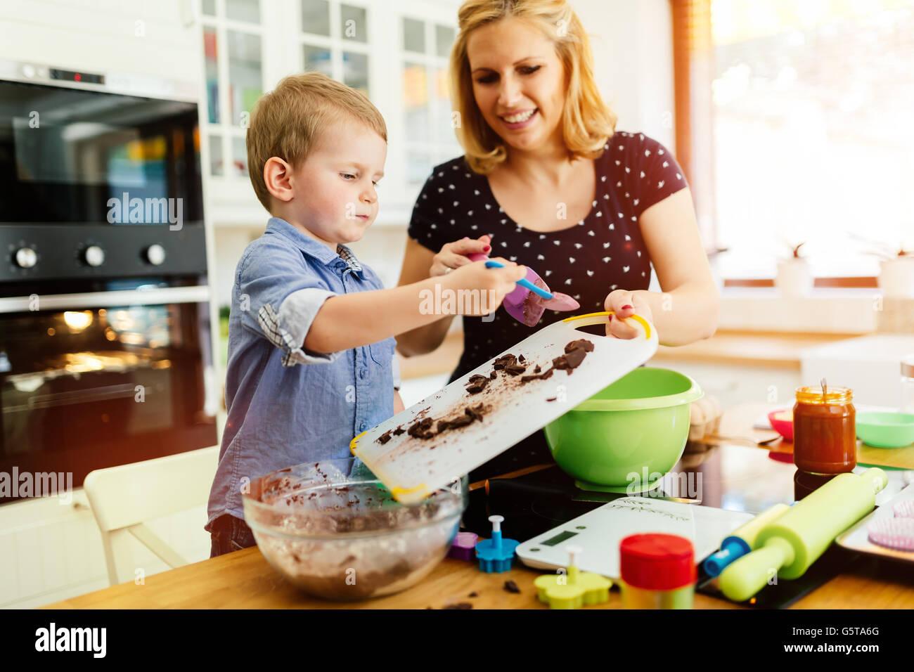 Bel bambino e la madre la cottura in cucina con amore Immagini Stock