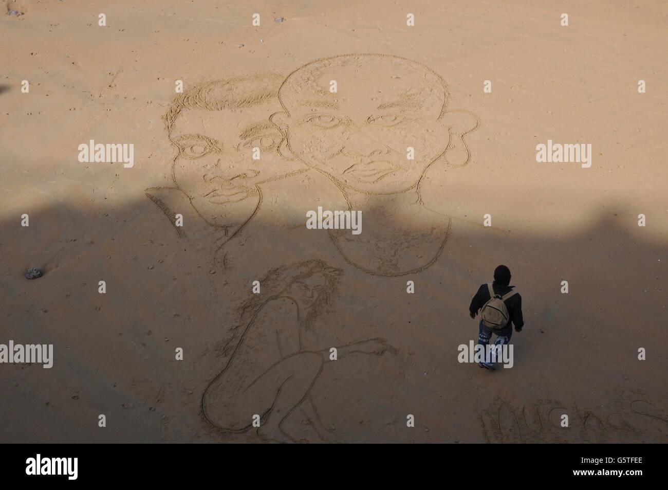 L'artista sta accanto a due facce gigante tracciata sulla spiaggia, Playa de la Concha. Immagini Stock